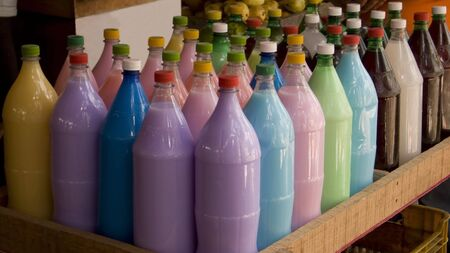 Bottles with colorful local drinks on a market. Shallow dof, focus is on the front row
