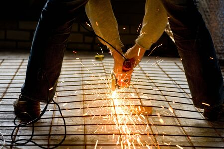 Construction worker cutting a construction net with an Angle grinder
