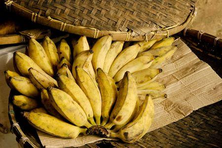 Bananas lying on a bamboo plate with cardboard Stock Photo