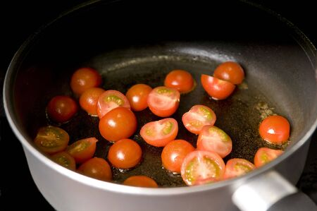 Small tomatoes being cooked in a pan, shallow dof Stock Photo