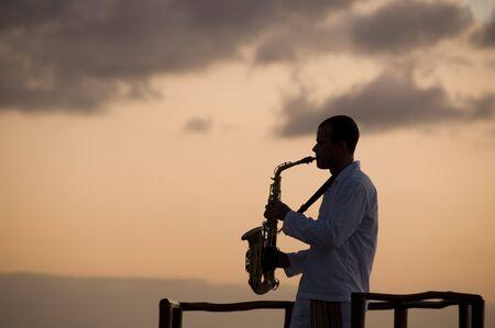 saxophonist: Man playing  saxophone at sunset