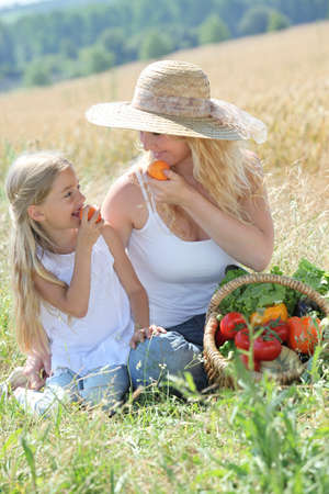 Mother and little girl eating fruits in garden photo