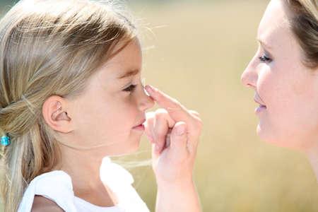 Madre e hija poniendo protector solar en su cara