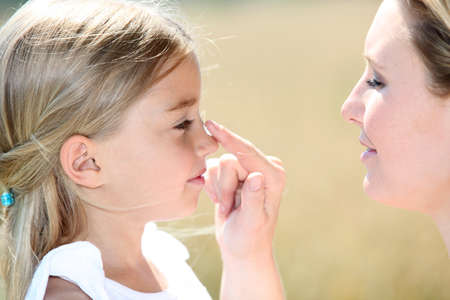 sun protection: Mother and daughter putting sunscreen on their face Stock Photo