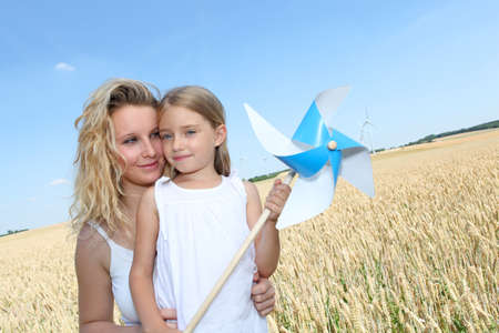 windy energy: Mother and daughter in wheat field Stock Photo