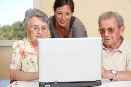 Couple of elderly persons with young woman using internet photo