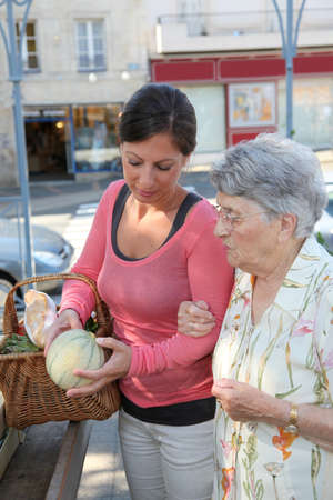 carer: Young woman helping elderly woman with grocery shopping