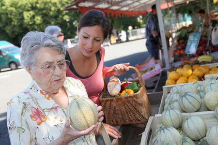 groceries: Mujer joven ayudando a la mujer de edad avanzada con las compras de comestibles  Foto de archivo