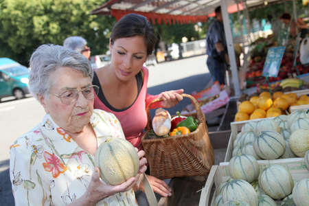 home help: Young woman helping elderly woman with grocery shopping