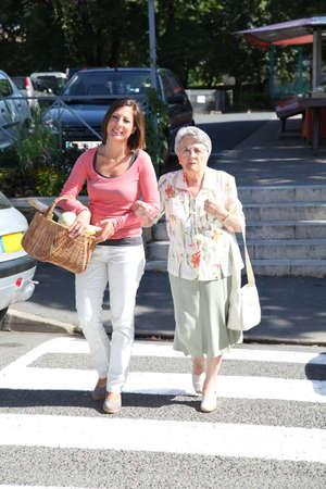 senda peatonal: Cuidadora dom�stica con la persona de edad avanzada en la ciudad  Foto de archivo