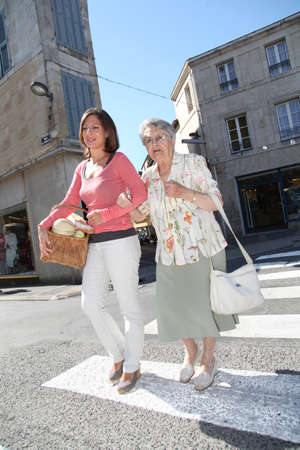 crosswalk: Home carer with elderly person in town