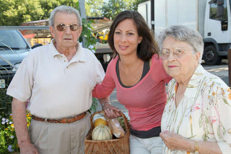 Closeup of young woman with couple of elderly persons photo
