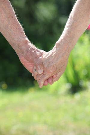 Closeup of elderly couple holding hands photo