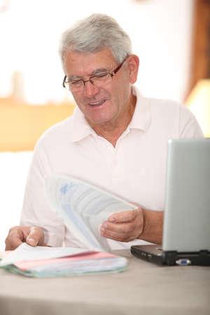 tax return: Senior man doing tax return on internet Stock Photo
