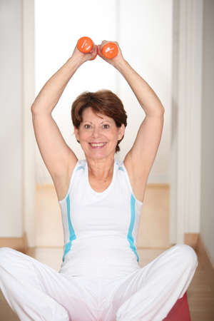 Closeup of senior woman lifting weights photo