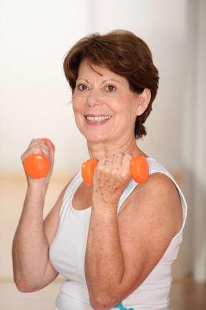 vertical wellness: Closeup of senior woman lifting weights