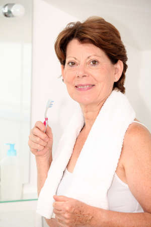 dentalcare: Closeup of senior woman with toothbrush in bathroom Stock Photo
