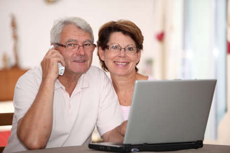 Senior couple at home with laptop computer photo