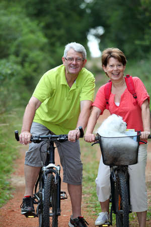 Senior couple riding bicycle in countryside photo