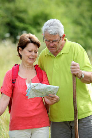 ramble: Closeup of senior couple rambling in countryside with map