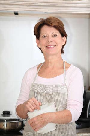 Closeup of senior woman standing in kitchen photo