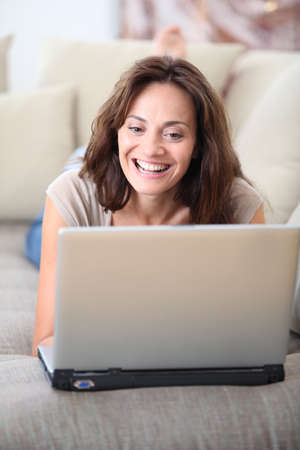 Woman on couch with laptop computer photo