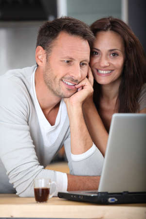 Couple at home connected on internet with laptop computer photo