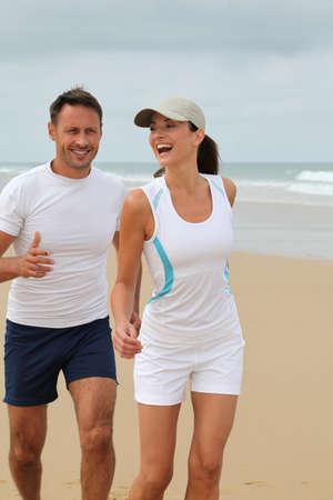 hombres haciendo ejercicio: Pareja de jogging en una playa de arena