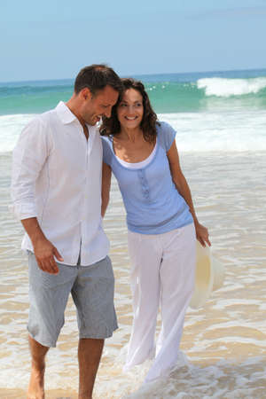 Couple walking on the beach photo