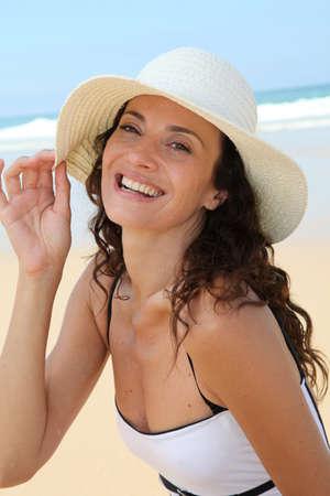 chapeau de paille: Belle femme assise sur la plage avec un chapeau de paille