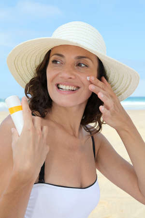 Beautiful woman at the beach putting sunscreen on her body photo