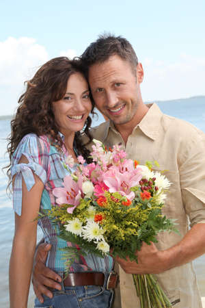 Man surprising woman with bunch of flowers Stock Photo - 7577722