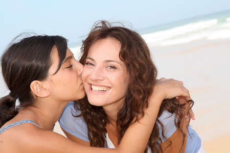 mom daughter: Closeup of young girl kissing her mom at the beach
