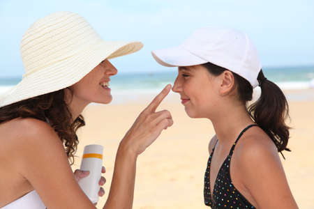 sun protection: Mother and daugther at the beach  Stock Photo