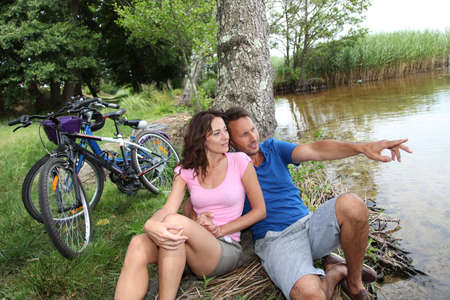 Couple resting by a lake photo