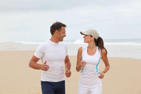 Couple jogging on a sandy beach photo