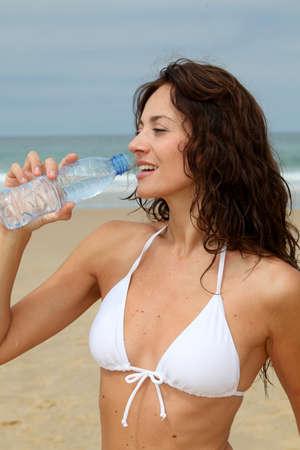 Beautiful woman drinking water at the beach  photo
