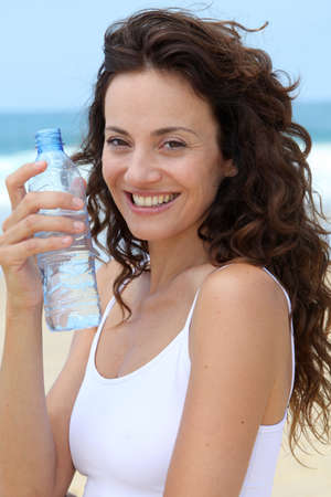 Beautiful woman drinking water at the beach  photo