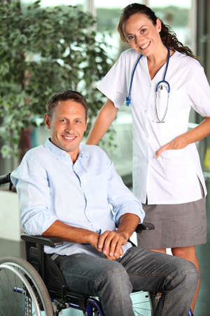 Man in wheelchair with doctor in hospital photo