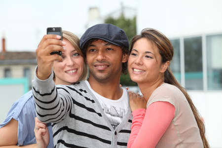 Group of friends taking picture with mobile phone photo