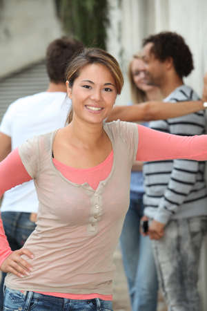 amongst: Closeup of beautiful young woman amongst group friends Stock Photo