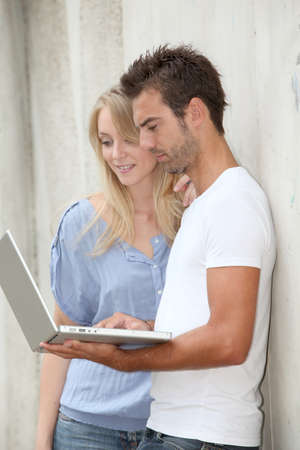 Couple standing against a wall with laptop computer photo