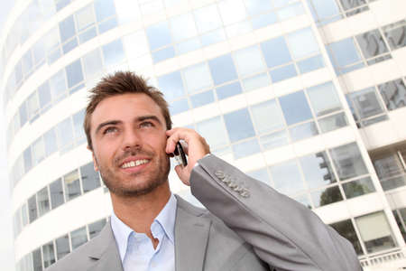 phonecall: Businessman standing in front of building with telephone