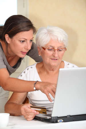 Elderly woman and young woman shopping on internet photo