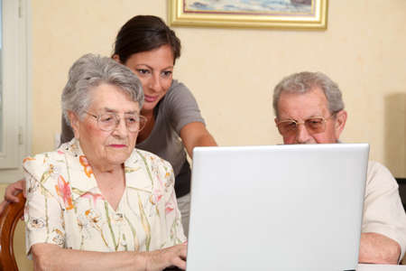 Couple of elderly persons with young woman using internet Stock Photo - 7695495