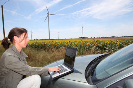 agronomist: Agronomist with computer in field with wind turbines