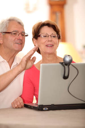 Closeup of senior couple sending messages through webcam photo