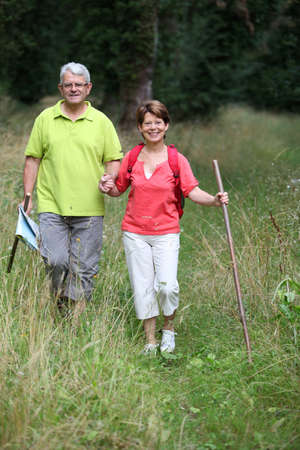 rambling: Senior couple rambling in countryside hand in hand