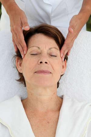 Senior woman having a face massage photo