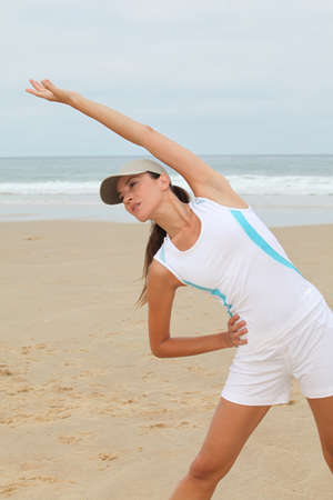 Woman doing exercises on the beach photo